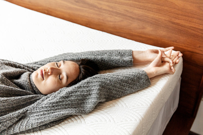 Young woman sleeping with arms extended on top of active-cooling mattress topper