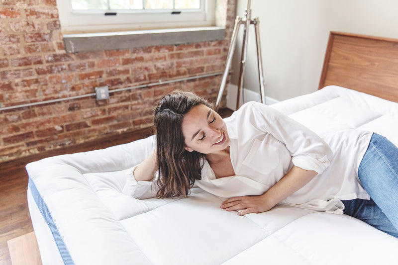 Happy woman relaxing on her mattress topper in room.