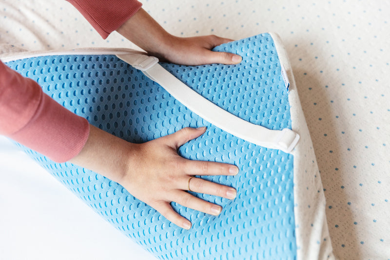 Hands pulling up the corner of the Select mattress topper to show the non-slip mesh on the bottom and adjustable straps