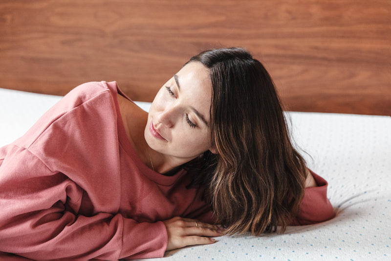 Young woman in pink sweatshirt lying on her new select high density mattress topper