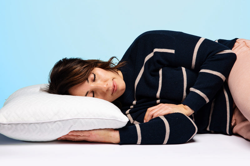 A woman laying on her side, resting her head on an active dry pillow