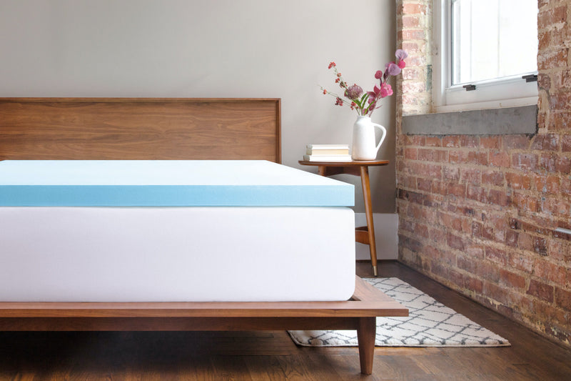 Gel-infused memory foam mattress topper on a mattress and bed frame in a studio apartment