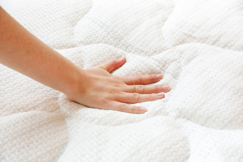 Hand pressing down on anti-static mattress pad to feel anti-static properties