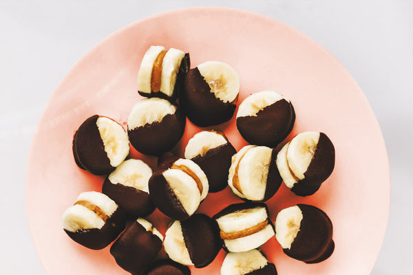 bananas dipped in chocolate on a pink plate