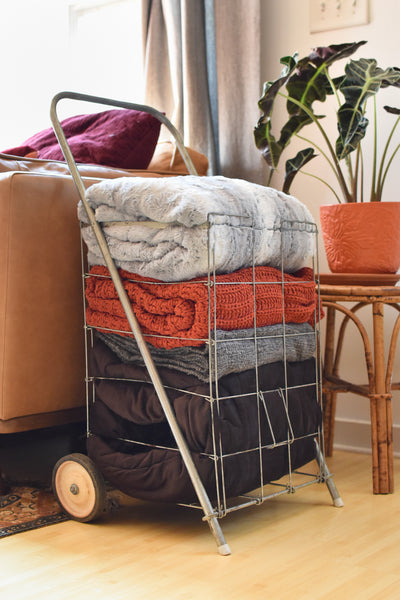 a stack of folded blankets in a repurposed vintage cart