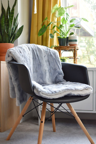 folded blanket laid over seat and back of chair