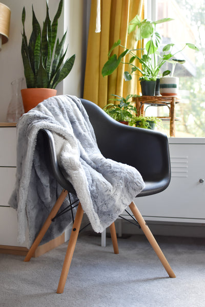 grey blanket draped over back, seat, and arm of chair