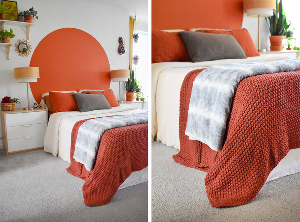 grey blanket folded and placed at foot of bed and layered over folded orange blanket
