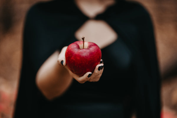 Woman dressed in all black with a black cape holding out a red apple.
