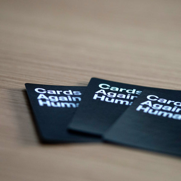 black cards against humanity cards laid out on wood table
