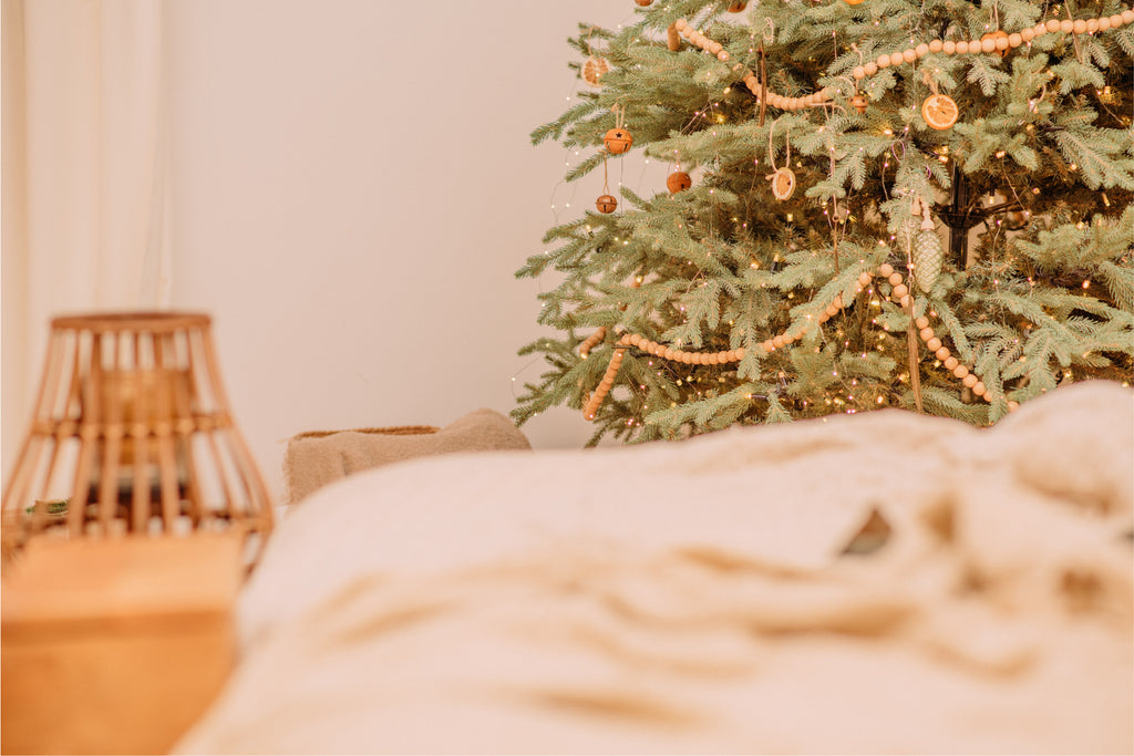 unmade bed and Christmas tree