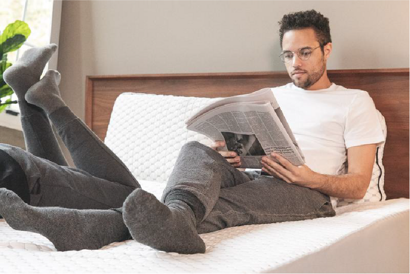 man sitting on bed reading the paper
