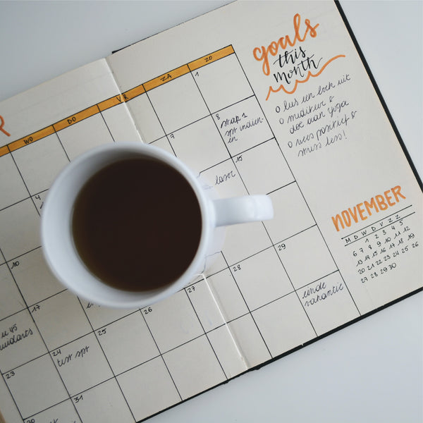 planner book with a cup of coffee on top