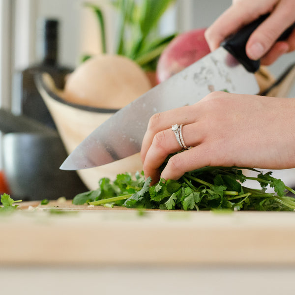 woman chopping up herbs on cutting bored