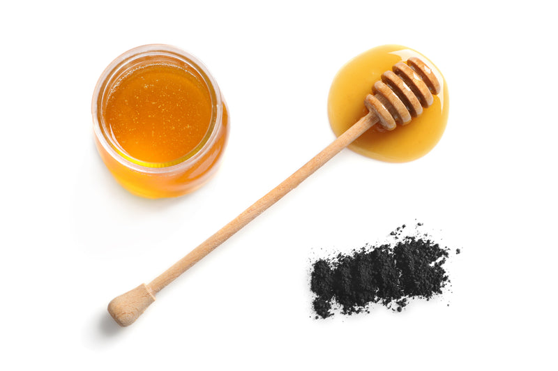 Photo of a jar of honey beside a teaspoon of activated charcoal