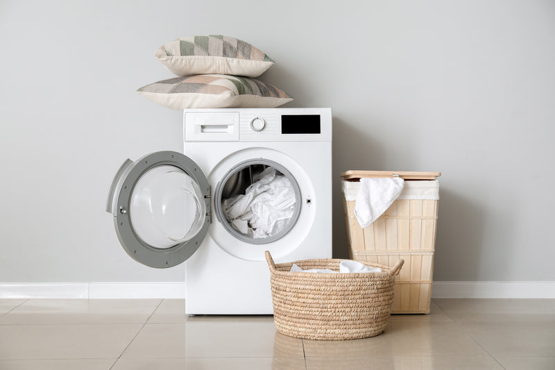 Front-load washing machine with door open to see mattress pad inside ready for laundering