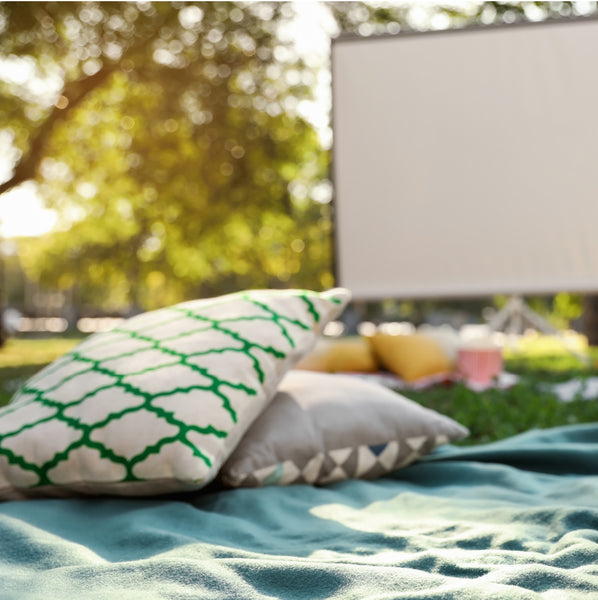 blankets and pillows laid out on grass with movie projector screen in the background