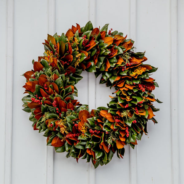 fall colored wreath hanging on white wall