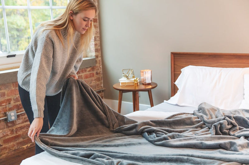 Woman laying gray fleece blanket out on bed.