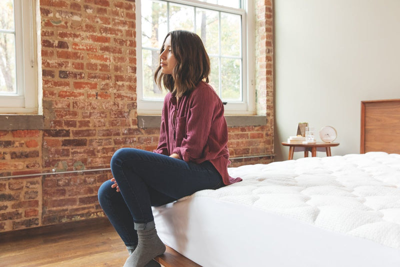 woman sitting on corner of bed with anti-static pad in place.