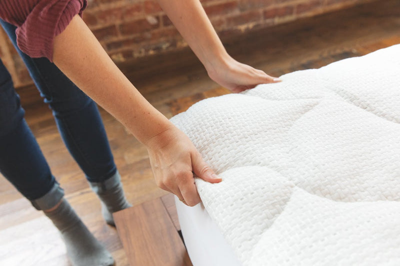 woman securing mattress pad to the bed with the skirt.  material looks soft and cool.