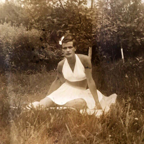 Person dressed as woman in skirt and halter top sitting on grass