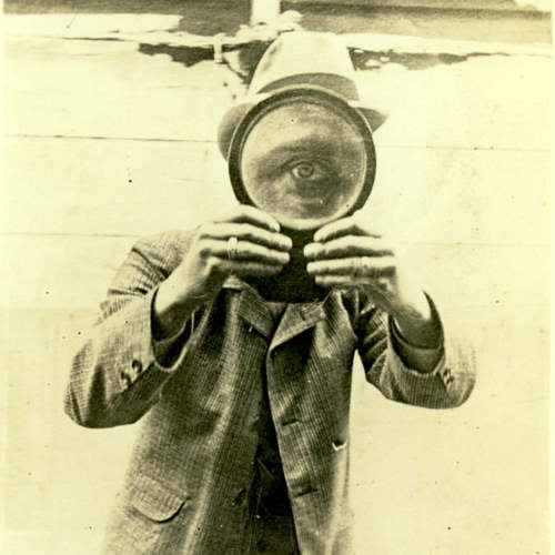 Man holding magnifying glass in front of eye