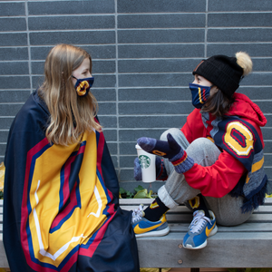 two women chat over a coffee with one warped in a Q sublimated fleece blanket
