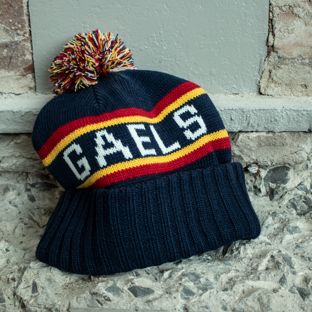 Knitted Tricolour Toque with embroidered Q and knitted Queen's on one side and Knitted Gaels on the opposite side. Tricolour pom adorns the top.
