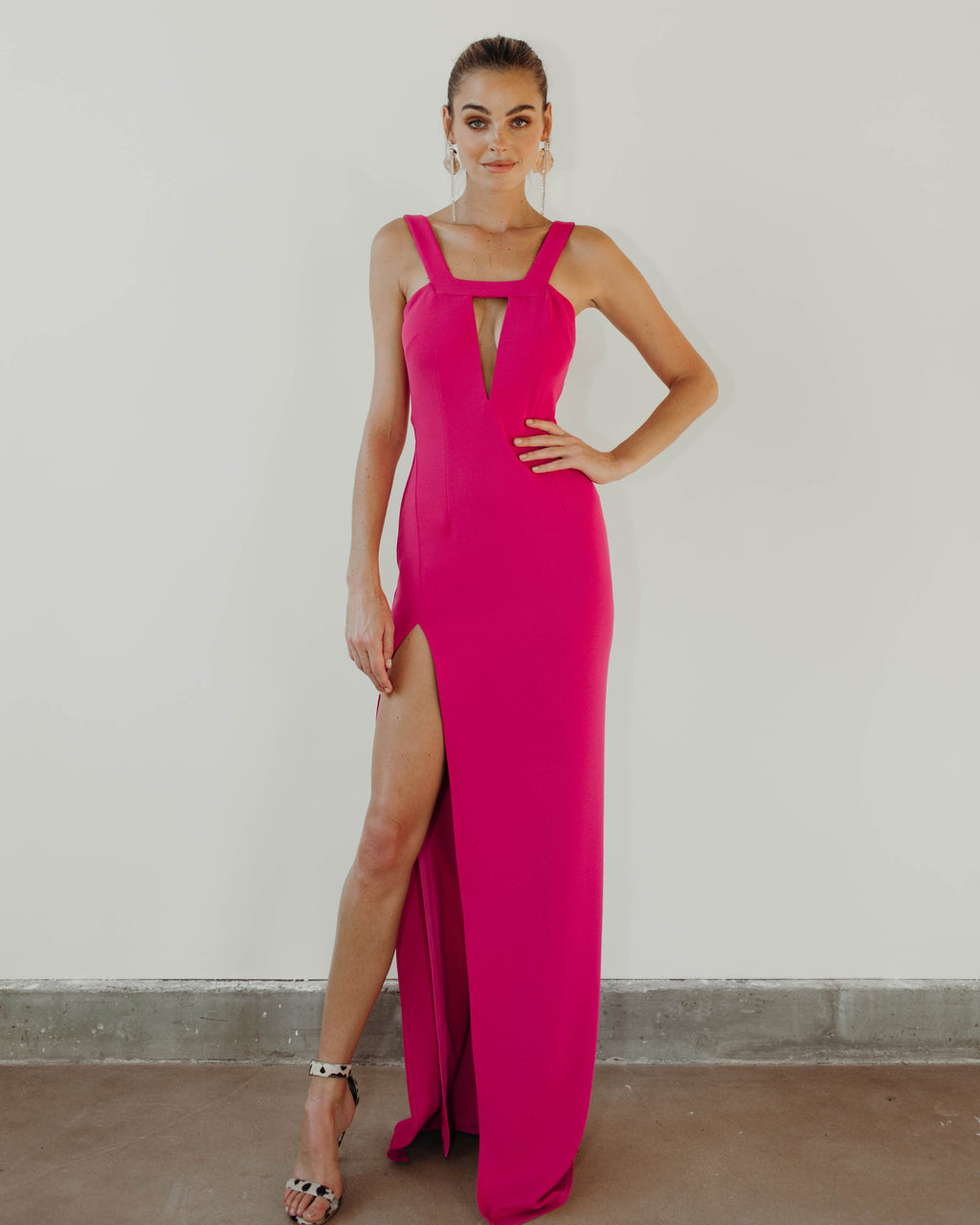 Model is wearing Take the Plunge gown in Pink Peacock by Katie May
