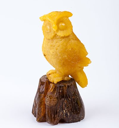 cute amber carving of an owl using two different colors of amber