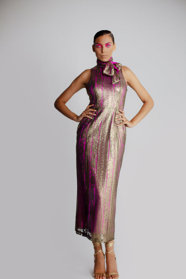 Model in gold lace sheath dress with bow and neck and v-back