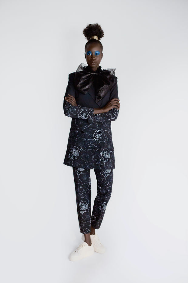 Model wearing black floral print relaxed cropped trousers