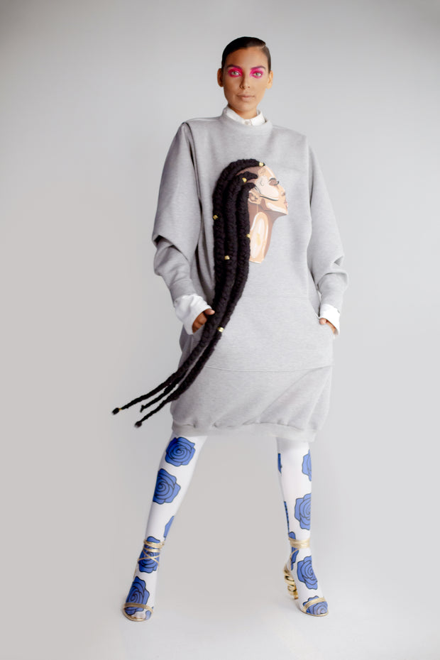 Model wearing heather grey sweatshirt dress featuring artwork by Taylor Ramsie of black woman with cornrows