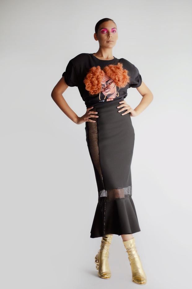 Model wearing black midi length skirt with sheer panels and fishtail