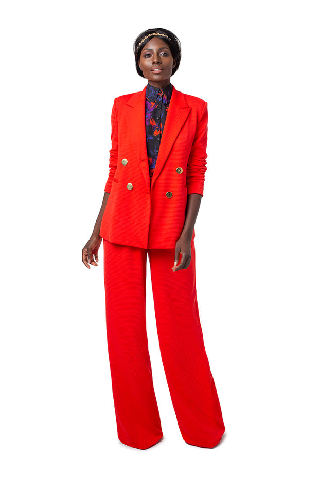 Front of model wearing red Ebi double breasted jacket with gold buttons