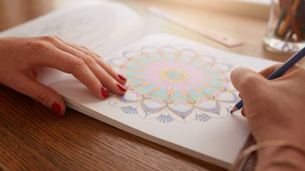 adult woman coloring madala pattern with coloring pencil in coloring book