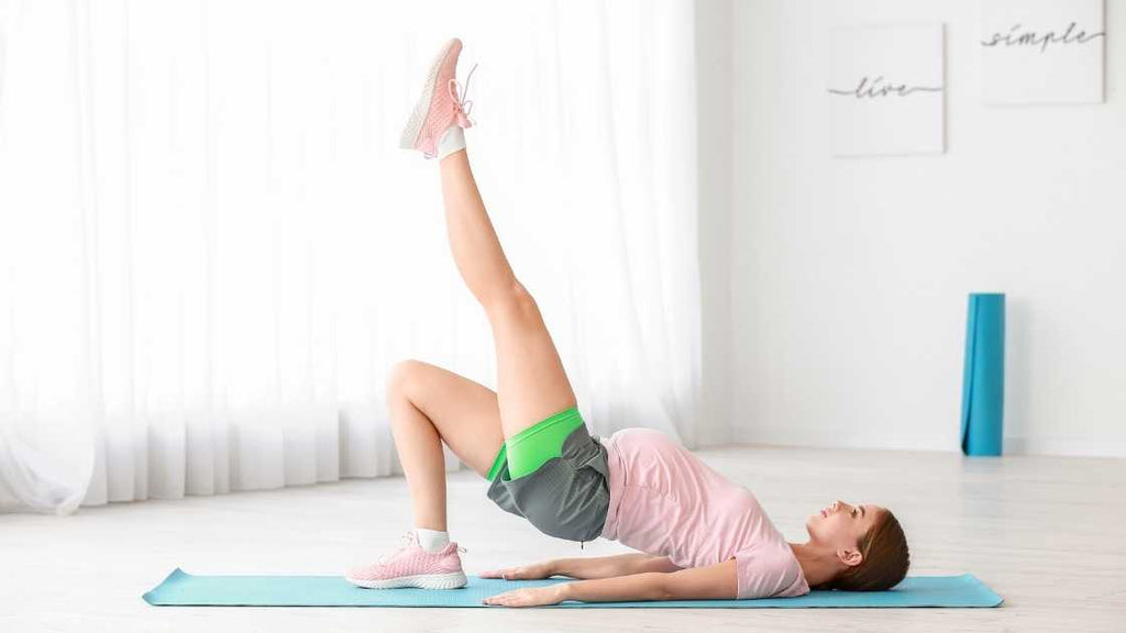 pregnant woman doing bridge with extended leg exercise