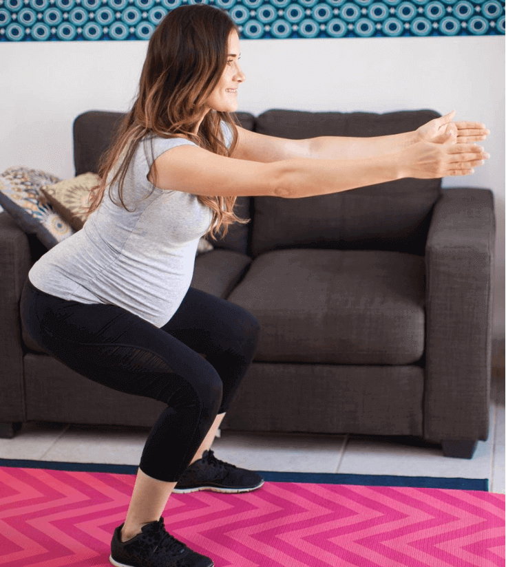 pregnant woman in starting squat position for get ups
