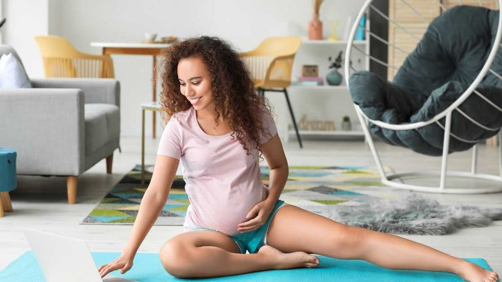 pregnant woman on floor at home reading SpeciallyMe's workout routines on laptop