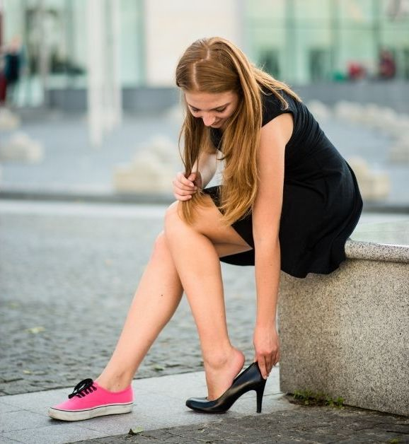 pregnant woman removing heels for flat shoes