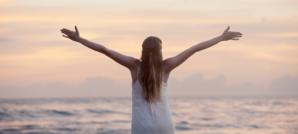 happy woman with arms outstretched looking out to sea