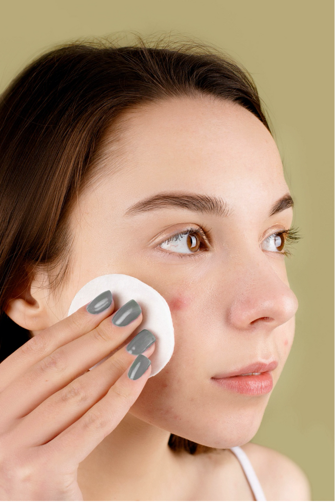 woman using cotton pad with facial cleanser or toner
