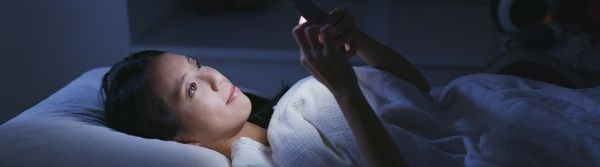 woman on bed looking at mobile phone