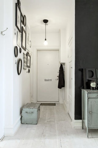 Small apartments can make use of pendant lights, like this narrow, monochromatic interior.