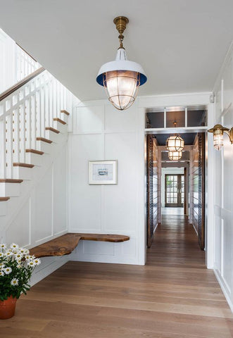 Coastal chic hallway with submarine inspired lighting.