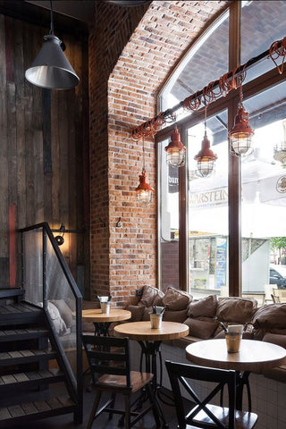 Elements such as wood textures, warm brick walls, industrial lights and concrete facades create a beautiful, honest backdrop for a modern restaurant interior.