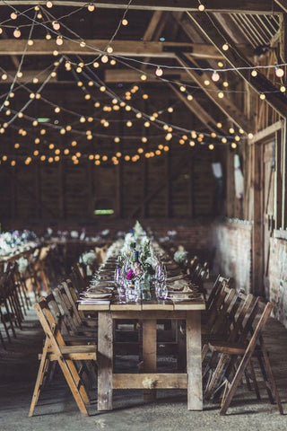 In this rustic wedding atmosphere, strings of festoon lights were recklessly woven upon another, creating a carefree canvas for a cosy barn wedding.