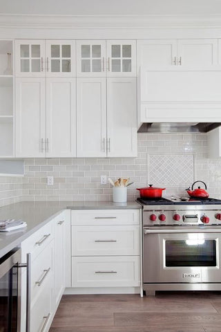 Light touches of ivory and egg shell whites are evident in this kitchen, accentuated by strong reds thanks to the selection of hardware and utensils.