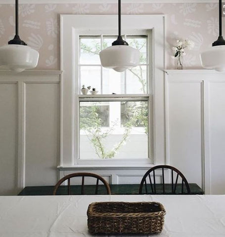 Schoolhouse lighting over dining table in the kitchen. The milky texture of schoolhouse lighting complements all-white rooms perfectly. It gives off that delicate, pastoral feell.